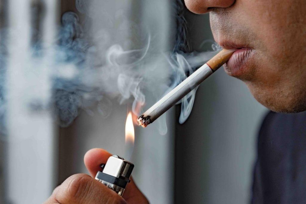 A person lighting a cigarette
